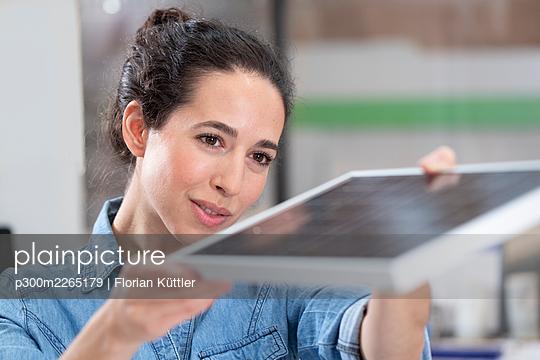 Female entrepreneur analyzing solar panel model at office - p300m2265179 by Florian Küttler