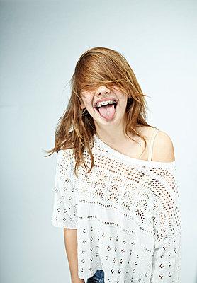 Weiblicher Teenager streckt die Zunge heraus - p1015m1515337 von Nino Gehrig