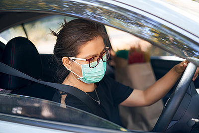 Woman wears a surgical mask and driving a car during the covid-19 - p1166m2235081 by Cavan Images