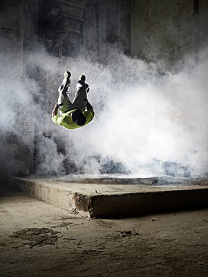 Man jumping in dust cloud during freerunning exercise - p300m2012468 von Christian Vorhofer
