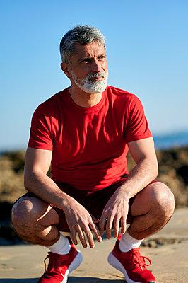 Mature man looking away while crouching on beach - p300m2275607 by Kiko Jimenez