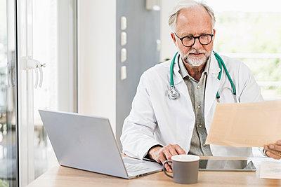 Male medical professional holding report at desk - p300m2294158 by Uwe Umstätter