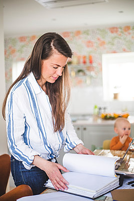 Busy female entrepreneur examining filed documents while daughter sitting in background at home office - p426m2117033 by Maskot