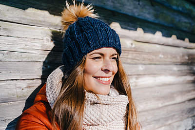 Young woman in winter clothing at log cabin - p586m2005082 by Kniel Synnatzschke