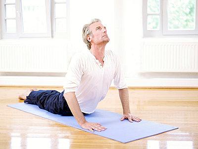 Mann beim Yoga  - p6430057 von senior images