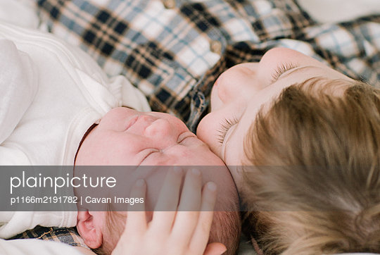 Big brother and newborn baby sister snuggling on bed - p1166m2191782 by Cavan Images
