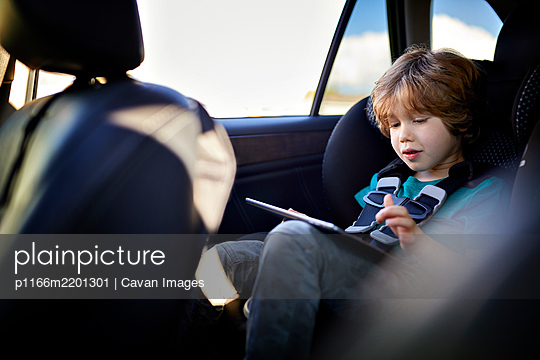 Cute boy using tablet PC while traveling in car - p1166m2201301 by Cavan Images