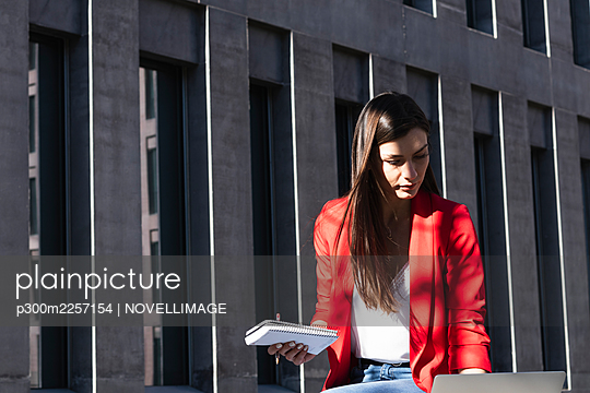 Businesswoman working on laptop while holding diary against structure - p300m2257154 by NOVELLIMAGE