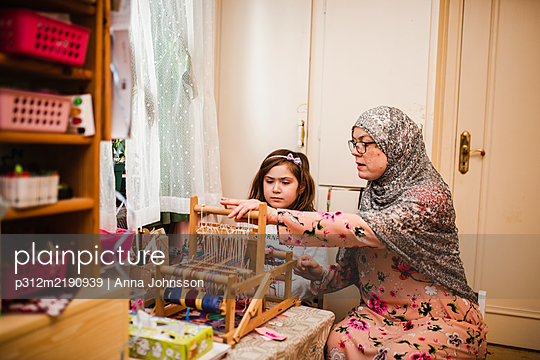 Mother with daughter using loom - p312m2190939 by Anna Johnsson