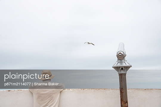 Man peering over a wall beside a telescope along the Algarve coast of southern Portugal, Europe - p871m2114077 by Shanna Baker