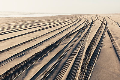 Tire tracks on the soft surface of sand on a beach.  - p1100m2085133 by Mint Images
