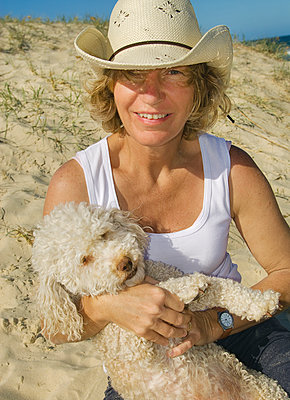 Woman and dog on beach - p1125m2013974 by jonlove