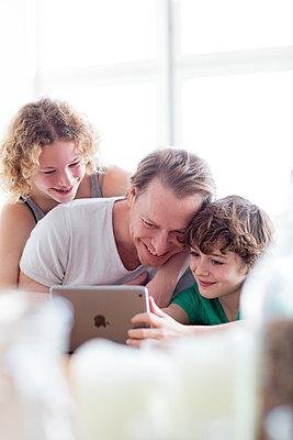 Vater mit Kids skypen in der Küche  - p1212m1094483 von harry + lidy