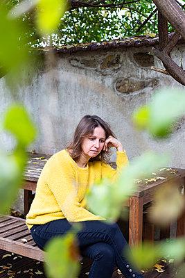 Sad woman sits in the garden - p1513m2224756 by ESTELLE FENECH