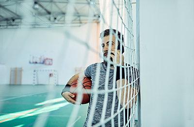 Man with basketball using smartphone behind net, indoor - p300m1588090 von Zeljko Dangubic