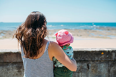 France, back view of mother and baby girl looking to the sea - p300m2004636 von Gemma Ferrando