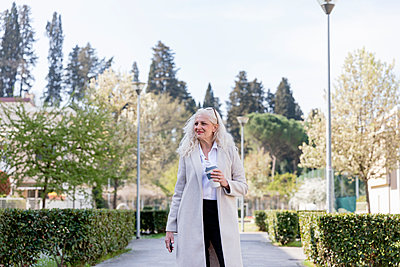 Smiling mature woman looking away while standing with reusable cup on footpath - p300m2274350 by Emma Innocenti