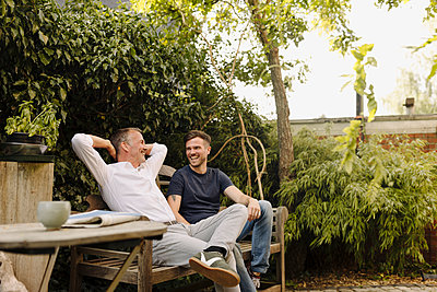 Father with hands behind head sitting by son on bench in backyard - p300m2275094 by Gustafsson