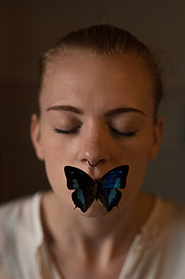 Young woman with butterfly on mouth - p552m1481761 by Leander Hopf