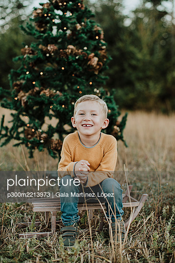 Smiling boy sitting on sled against Christmas tree at countryside - p300m2213973 by Gala Martínez López
