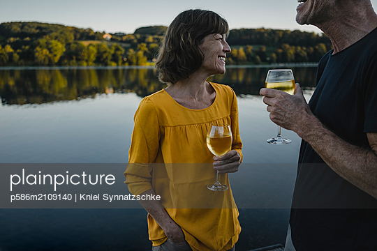 Mature couple drinking white wine at Lake Baldeneysee - p586m2109140 by Kniel Synnatzschke