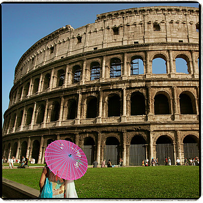 Woman holding a paper umbrella in front of the Colosseum, Rome, Italy - p1028m2027881 by Jean Marmeisse