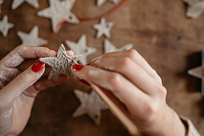hands of young woman creating clay star ornaments for Christmas - p1166m2235300 by Cavan Images