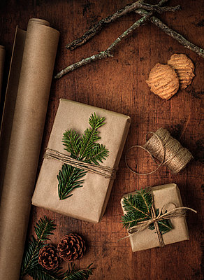 Pine fronds tied to Christmas presents - p1427m2163691 by Tetra Images