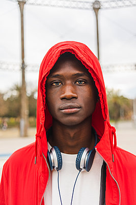 Portrait of a young black man wearing red hoodie - p300m2059783 by VITTA GALLERY