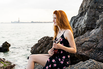 Smiling redheaded young woman sitting on rock near the sea playing ukulele - p300m2113786 by VITTA GALLERY