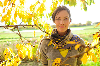 Portrait of woman at twigs with autumn leaves looking at camera - p300m2155821 by Eyecatcher.pro