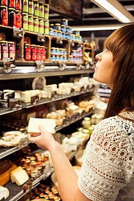 Woman shopping cheese in supermarket - p426m1017982f by Maskot