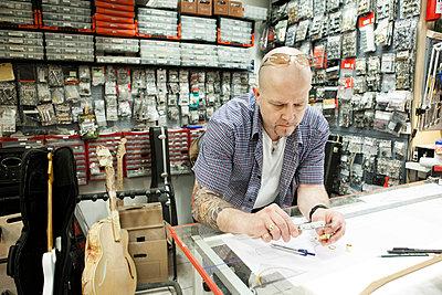 Guitar maker measuring up blueprint design in workshop - p429m942677f by Soren Hald