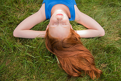 Caucasian girl laying in grass with hands behind head - p555m1303500 by JGI/Jamie Grill