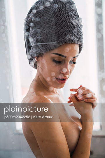 Barechested young woman with towel around her head at home - p300m2042252 by Kike Arnaiz
