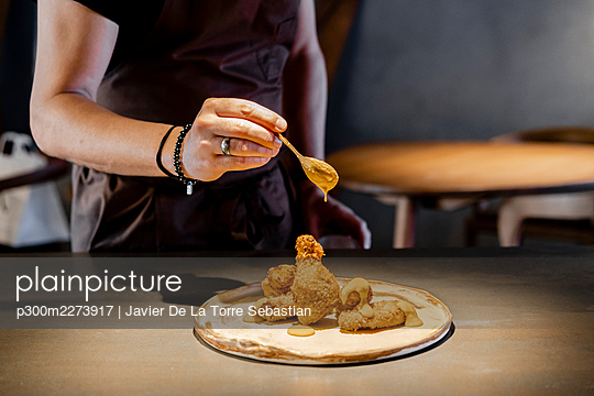 Male expertise pouring sauce on chicken nugget in restaurant - p300m2273917 by Javier De La Torre Sebastian