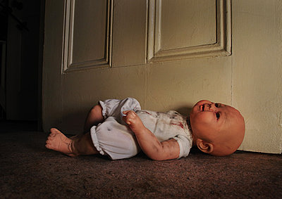 Broken doll laying next to door - p1072m829359 by Neville Mountford-Hoare