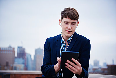A young man standing on a rooftop looking down at a tablet. - p1100m1216117 by Mint Images