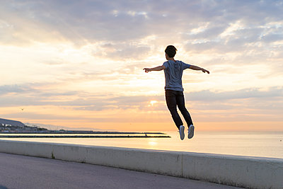 Young Chinese man jumping on wall at the beach - p300m2012290 von VITTA GALLERY