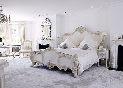 Ornately carved bed in carped bedroom of London home - p349m790421 by Brent Darby
