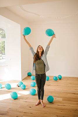 Young woman in new apartment playing with balloons - p586m1064891 by Kniel Synnatzschke