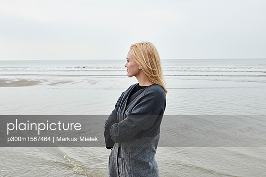 Netherlands, blond young woman standing on the beach looking at distance - p300m1587464 von Markus Mielek