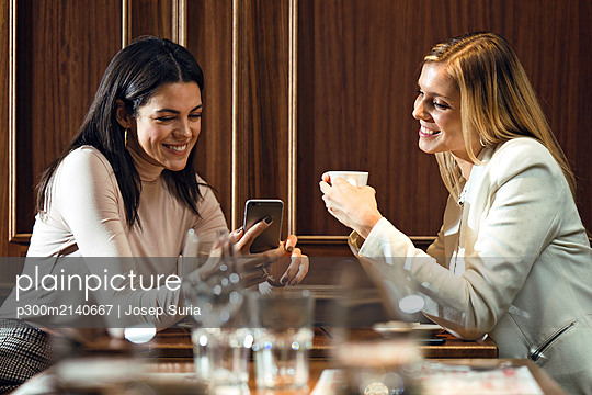 Two happy women in a restaurant looking at smartphone together - p300m2140667 by Josep Suria