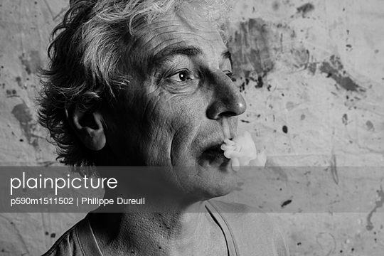 Man blowing smoke from an electronic cigarette - p590m1511502 by Philippe Dureuil