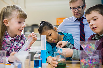 Teacher and elementary students conducting scientific experiment - p1192m1016683f by Hero Images