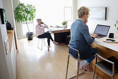 Woman using laptop in kitchen while senior mother talks on smart phone at table - p1192m2088379 by Hero Images