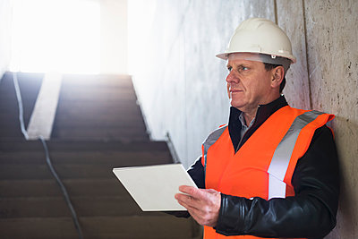 Man with tablet wearing safety vest in building under construction - p300m1460104 by Daniel Ingold