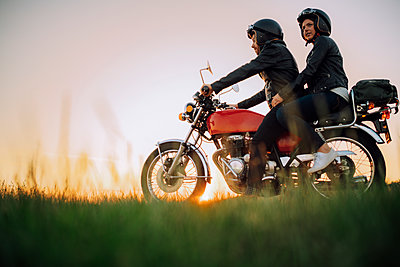 Young couple on vintage motorbike at sunset - p300m2143847 by Juri Pozzi
