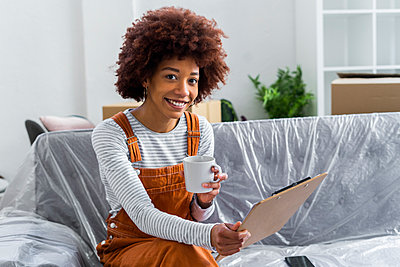 Smiling woman having coffee while holding checklist on clipboard in new home - p300m2251342 by Giorgio Fochesato