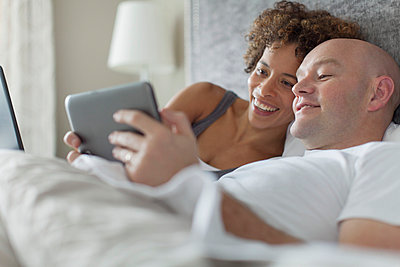 Married couple sharing tablet computer in bed. - p328m840946f by Hero Images